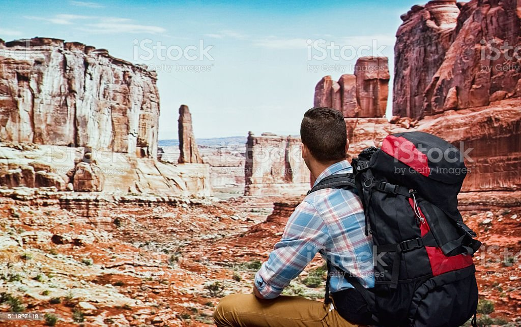 Rear view of hiker sitting in the mountain stock photo