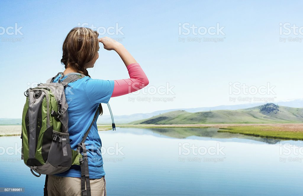 Rear view of hiker standing at lake & looking away stock photo