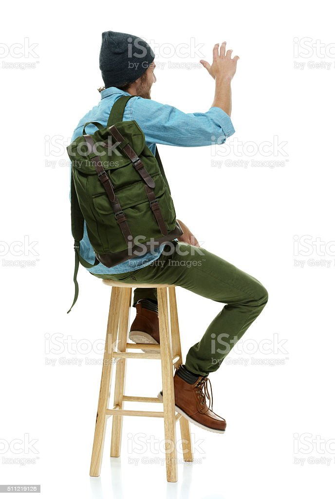 Rear view of hipster on stool and waving hand stock photo