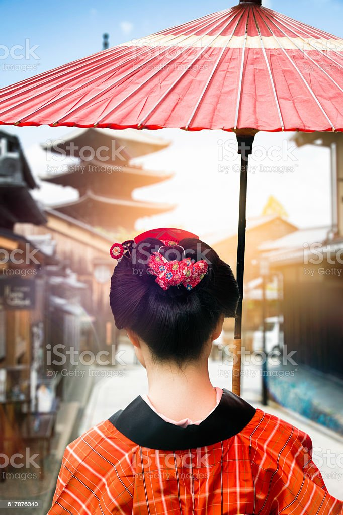 Rear view of Japanese lady walking under umbrella in Kyoto stock photo