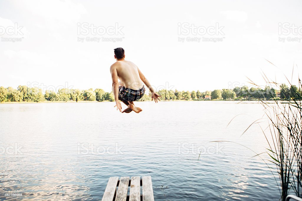 rear view of jumping young from jetty into a lake stock photo