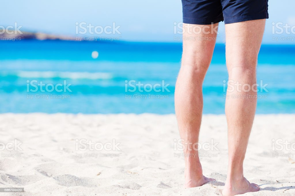 Rear view of legs on the beach stock photo