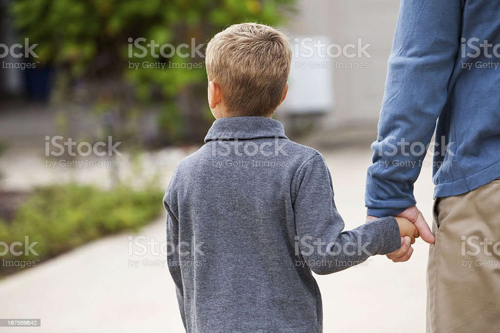 Rear view of little boy holding father's hand stock photo
