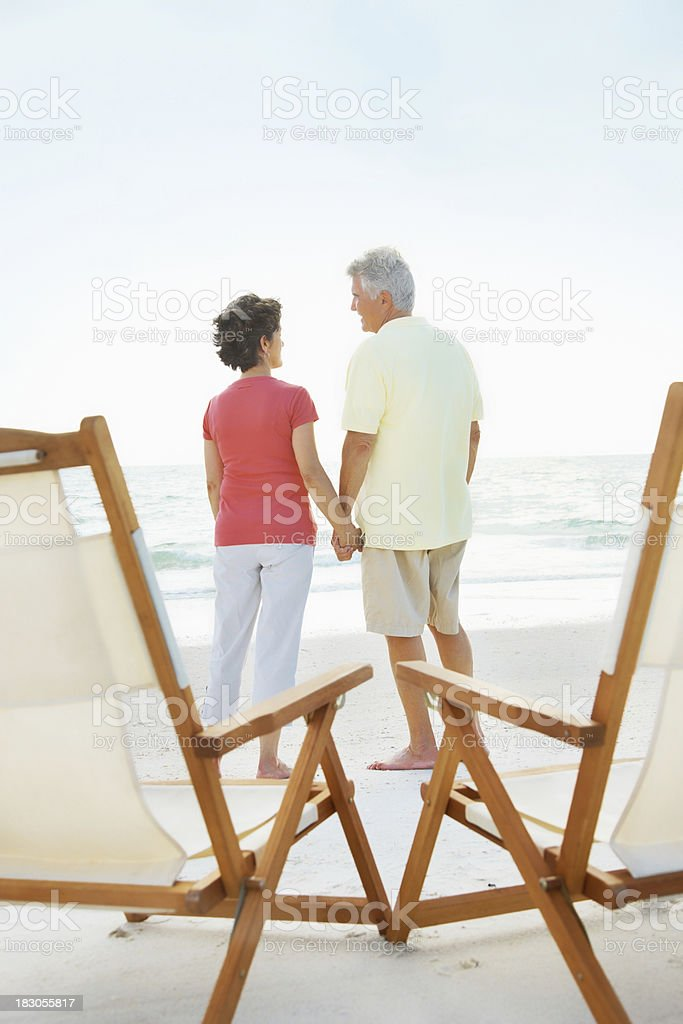 Rear view of loving senior couple holding hands on beach royalty-free stock photo