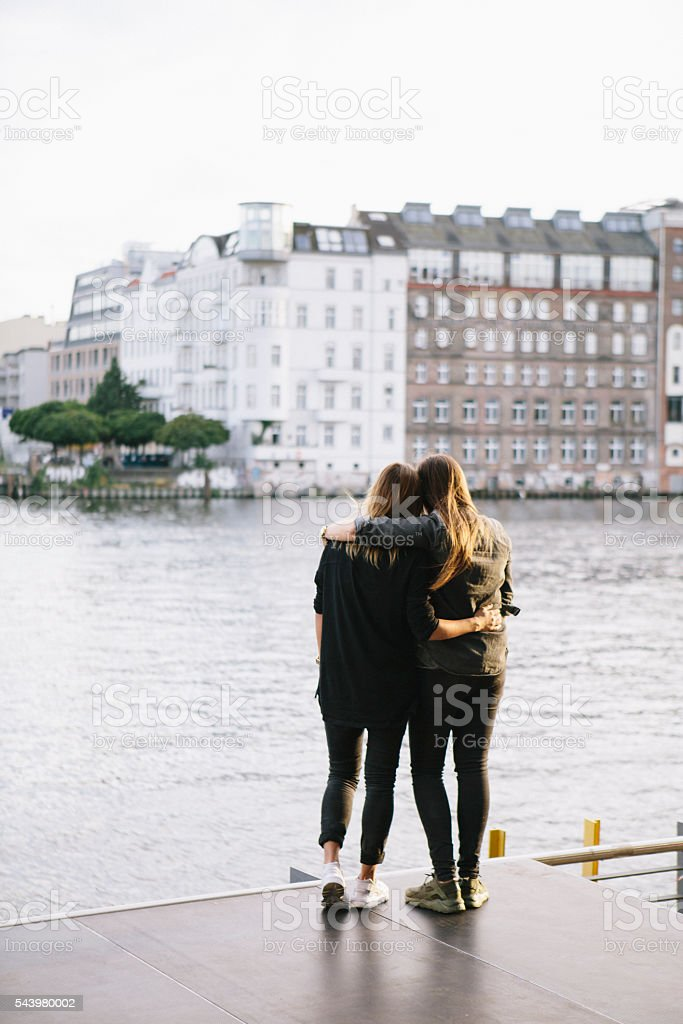 rear view of loving women couple in Berlin, embracing stock photo