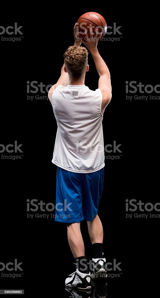 Rear view of male doing layup stock photo