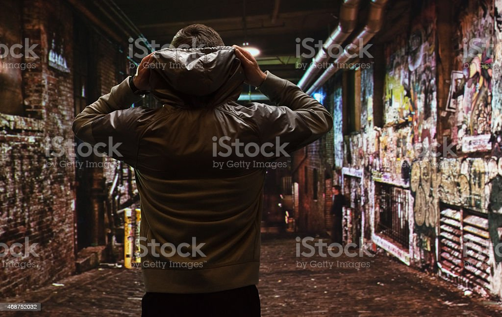 Rear view of male runner outdoors at night stock photo