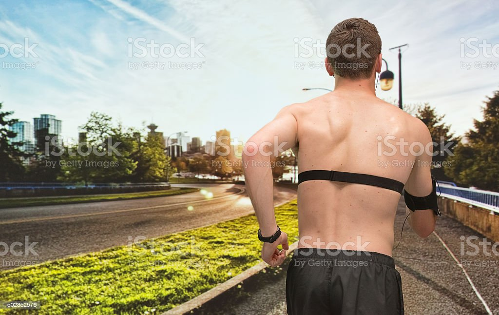 Rear view of male runner running outdoors stock photo