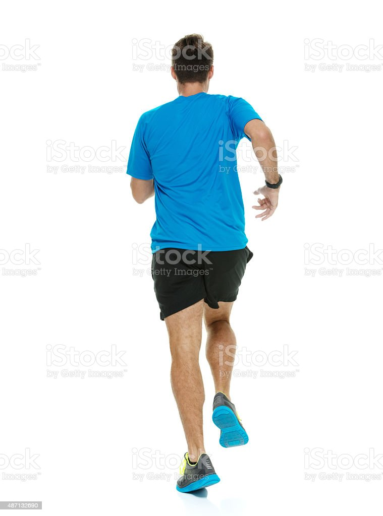 Rear view of male runner running stock photo