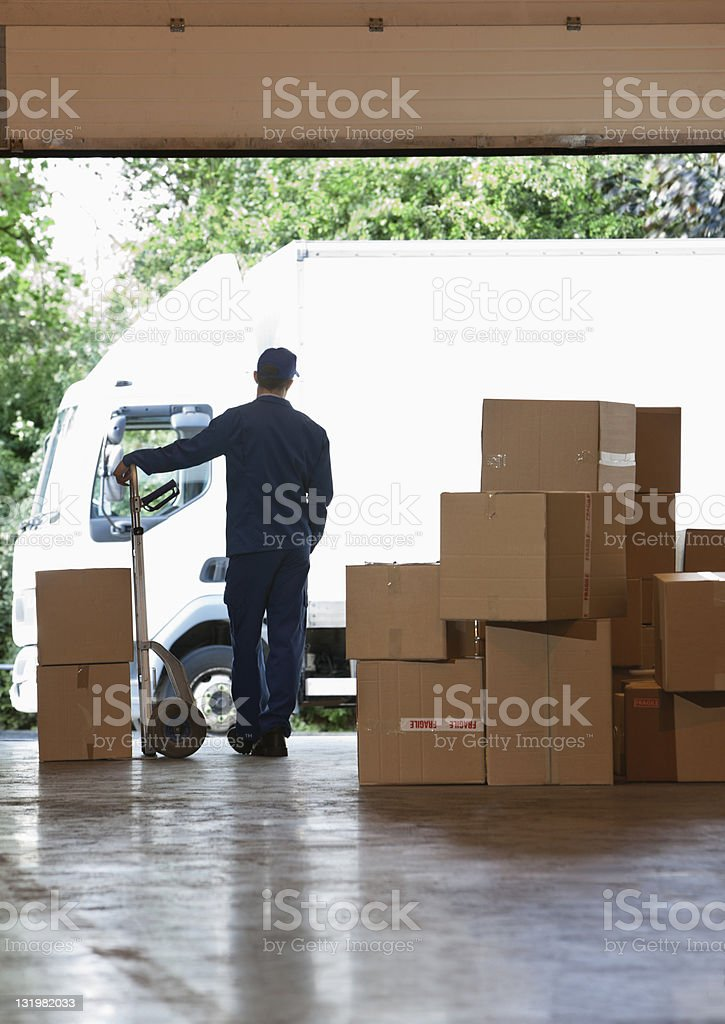 Rear view of male worker standing near cardboard cardboard boxes in warehouse stock photo