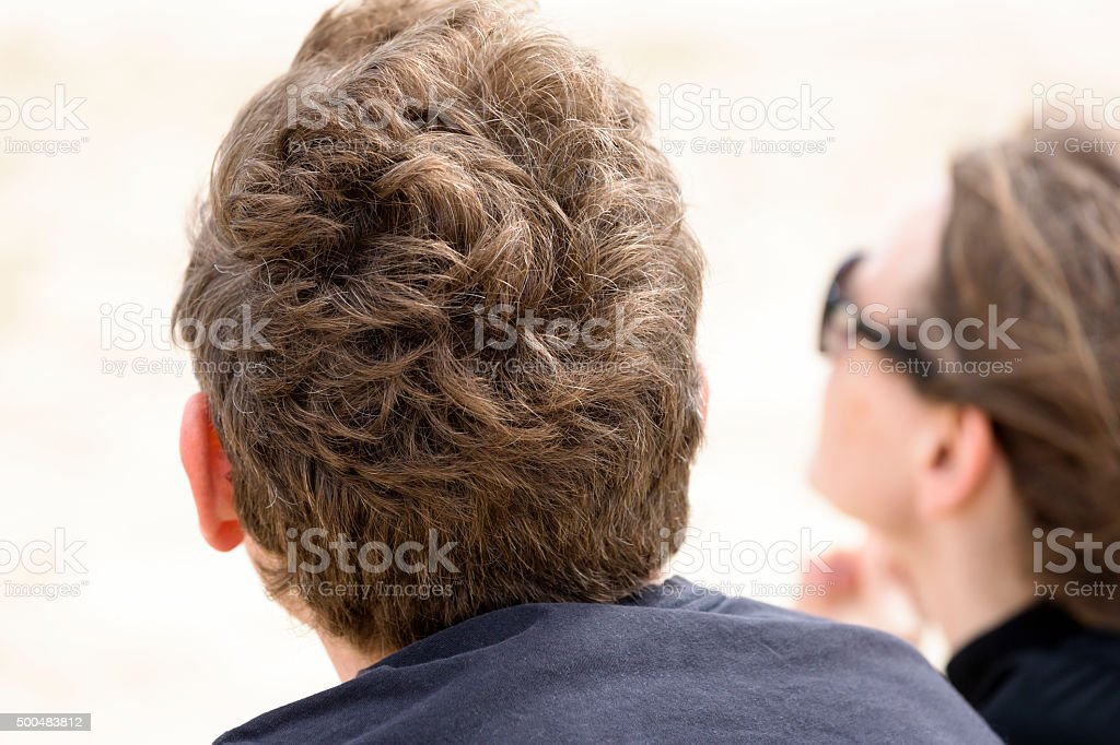 Rear view of man and female in distance looking up stock photo