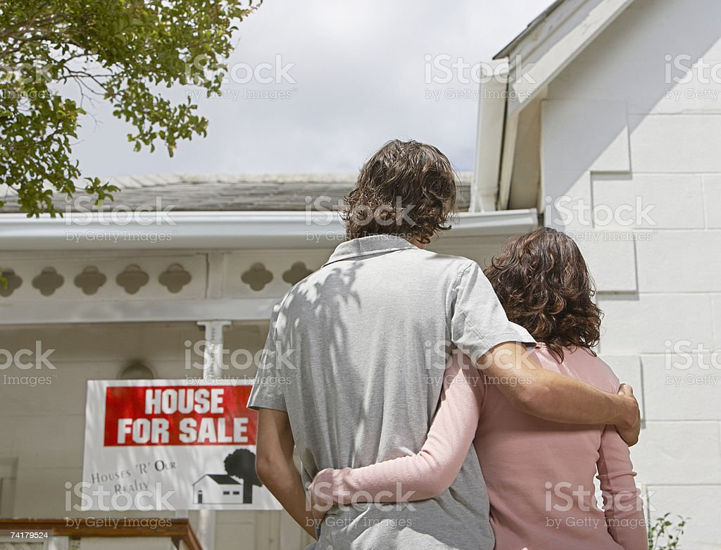 Rear view of man and woman standing in front of house with for sale sign royalty-free stock photo
