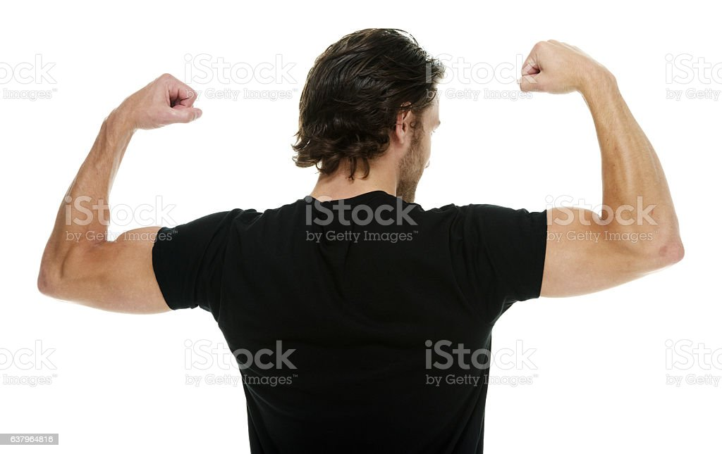 Rear view of man flexing muscle stock photo