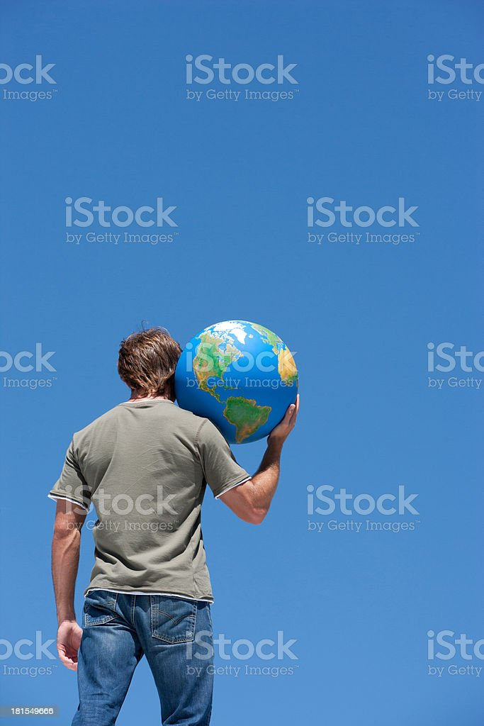 Rear view of man holding globe on shoulder outdoors stock photo