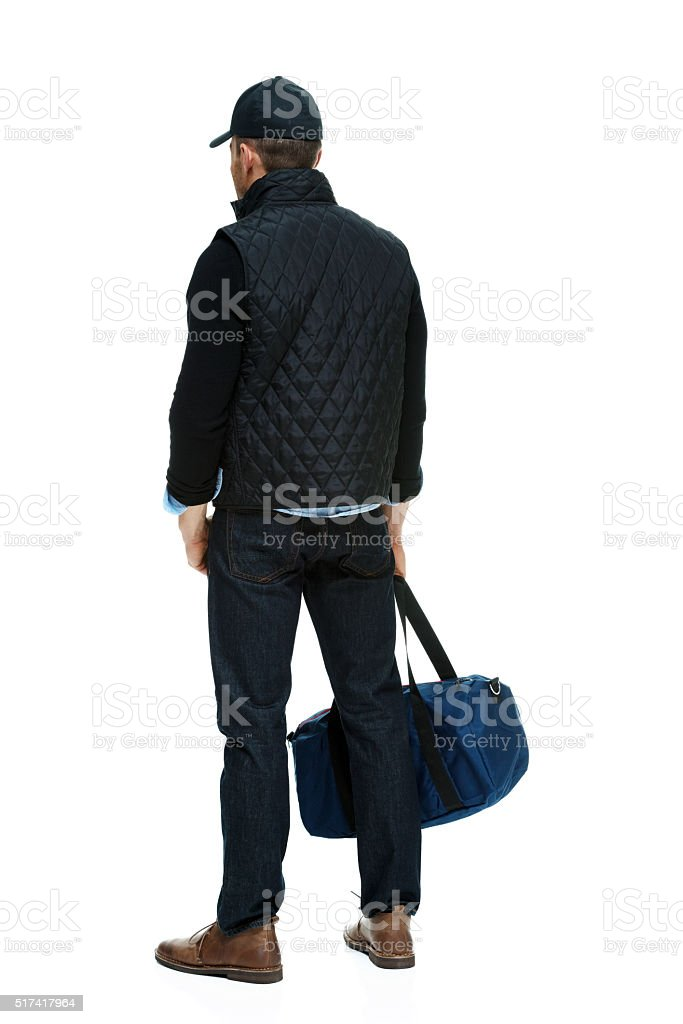 Rear view of man holding gym bag stock photo