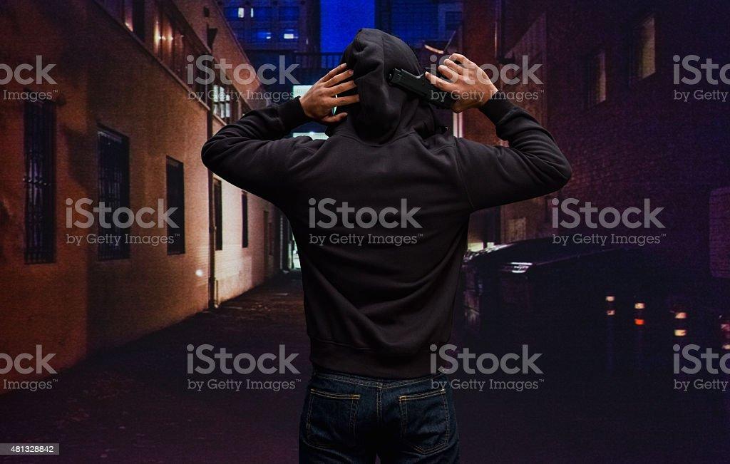 Rear view of man holding handgun stock photo