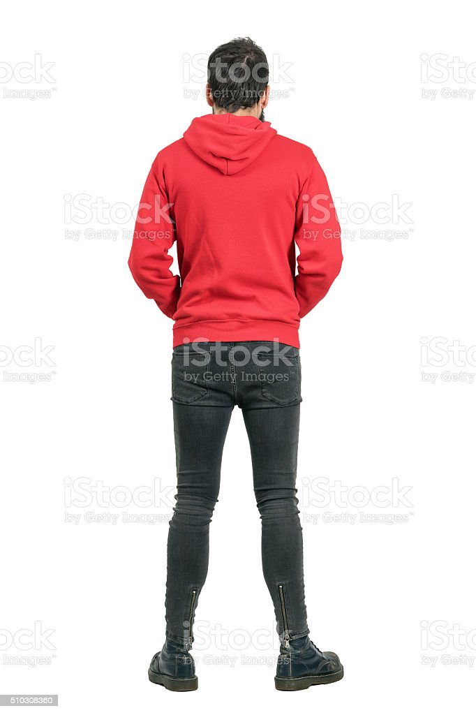 Rear view of man in jeans and boots wearing hoodie stock photo