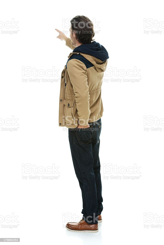Rear view of man in winter clothes and pointing stock photo