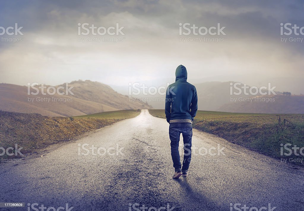 Rear view of man on country road stock photo