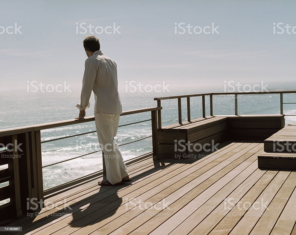 Rear view of man on deck looking at water royalty-free stock photo
