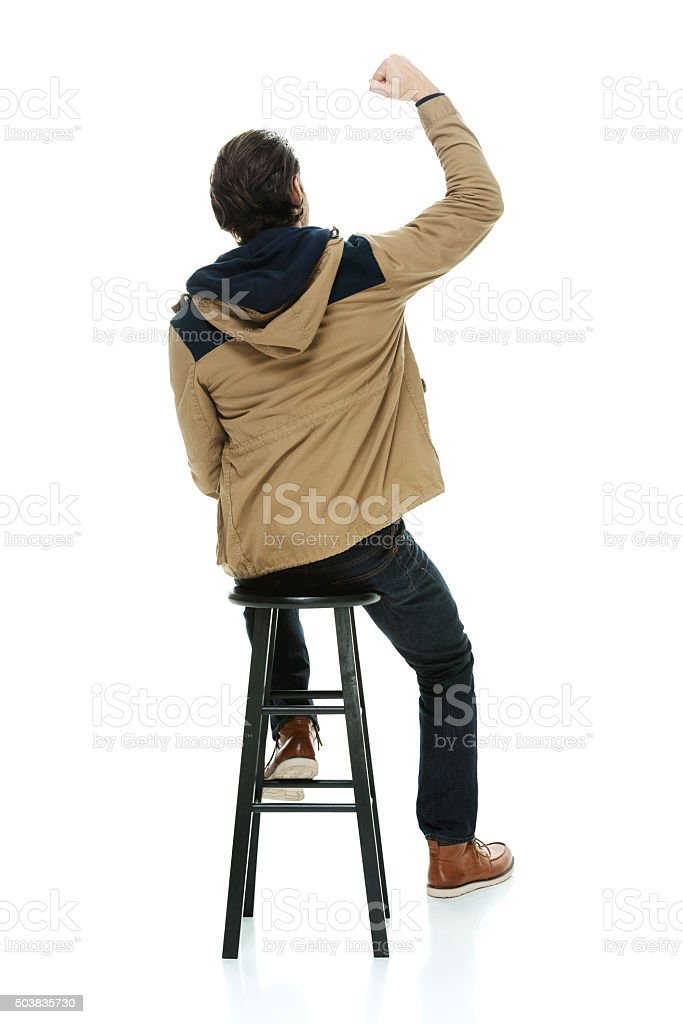 Rear view of man on stool and cheering stock photo