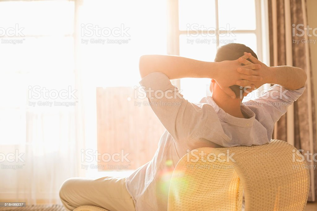Rear view of man relaxing on chair at home stock photo