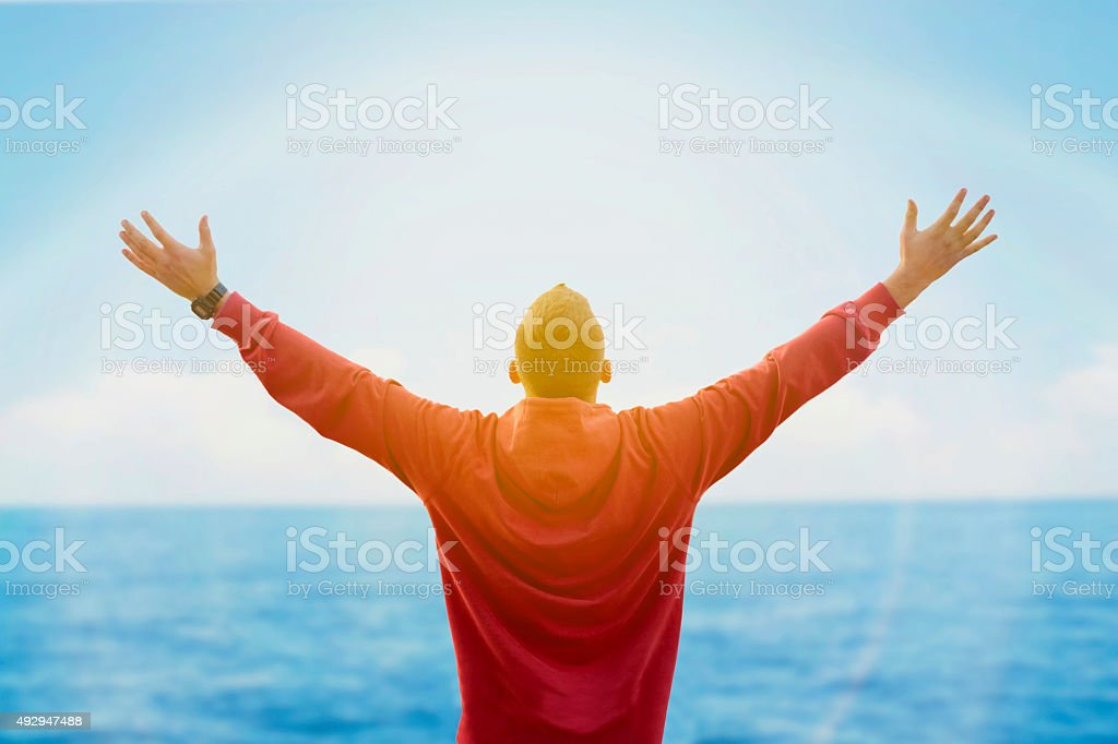 Rear view of man spreading arms and watching the ocean stock photo