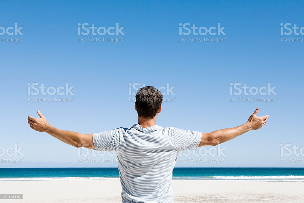 Rear view of man standing on beach looking out to sea with arms outstretched stock photo