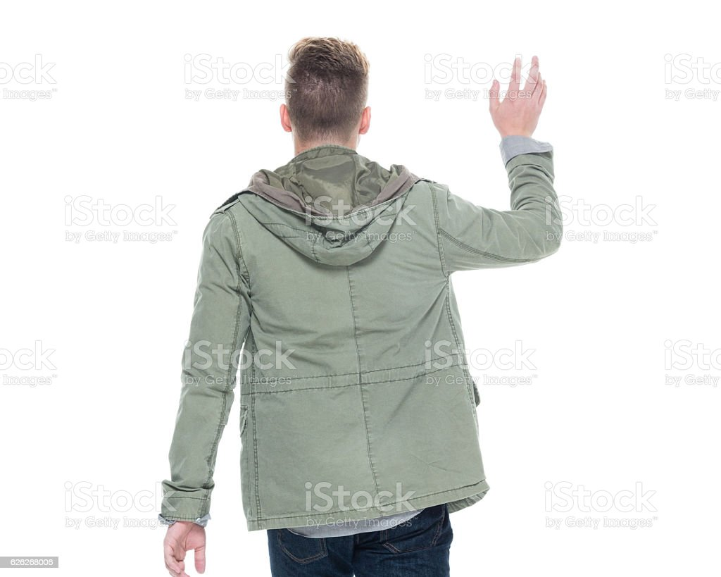 Rear view of man waving hand stock photo