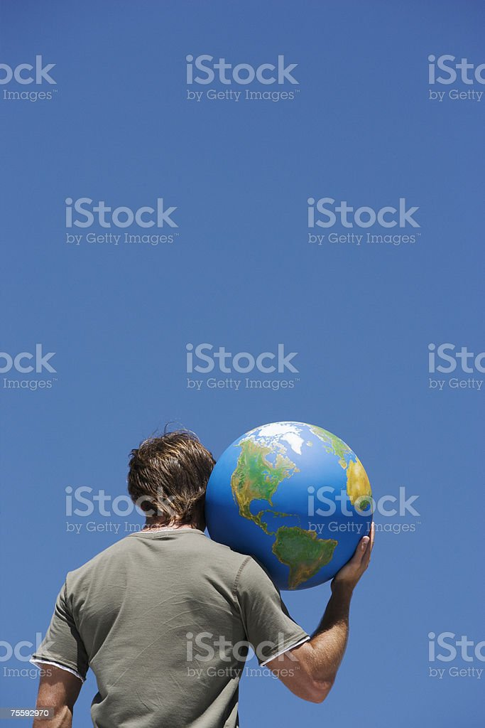 Rear view of man with globe on shoulder royalty-free stock photo