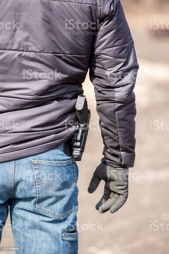 Rear View of Man With Pistol At His Waist stock photo
