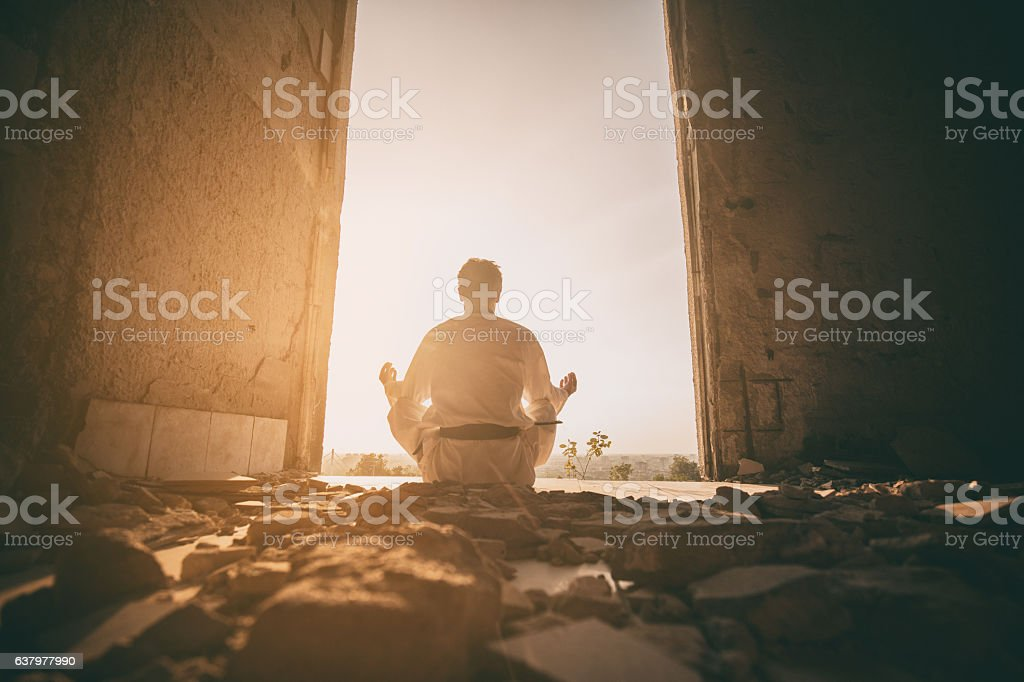 Rear view of martial artist practicing Yoga at sunset. stock photo