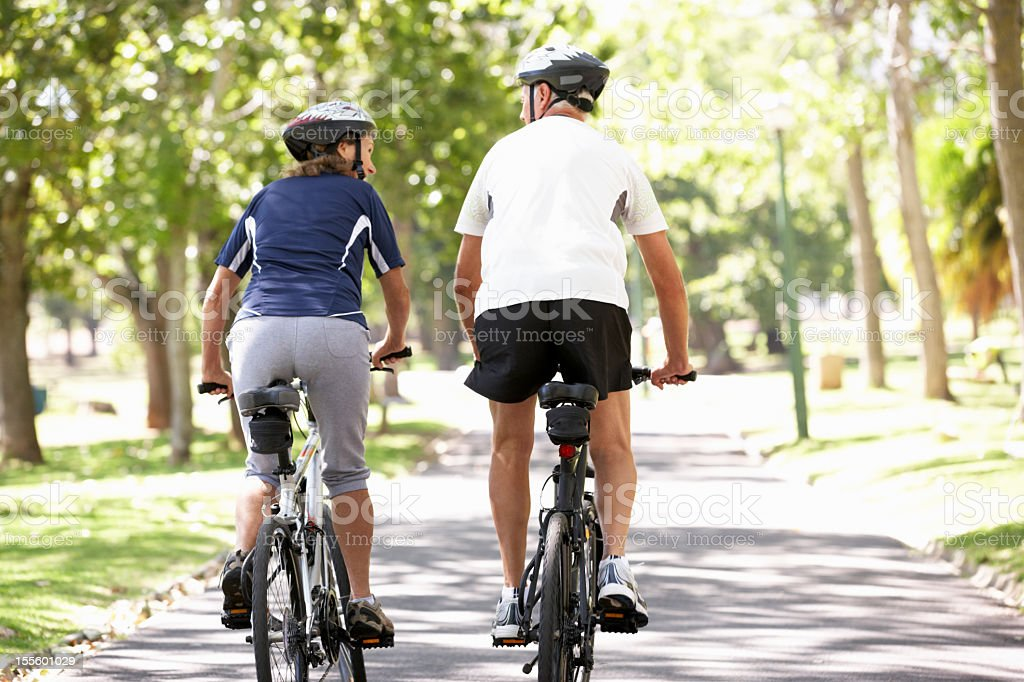 Rear View Of Mature Couple Cycling Through Park royalty-free stock photo