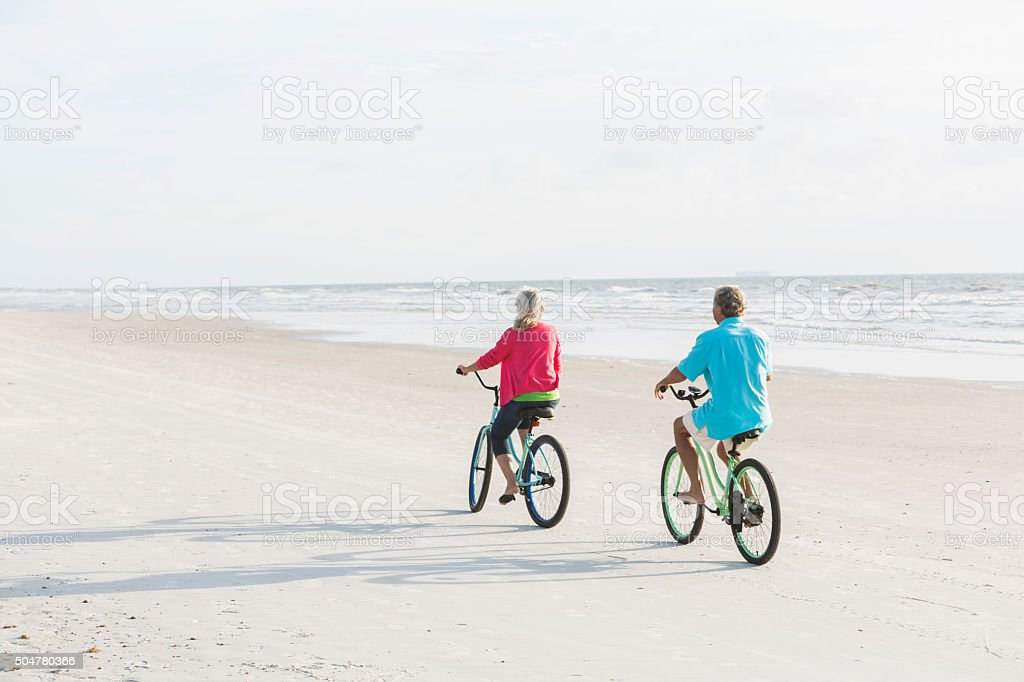 Rear view of mature couple riding bikes on the beach stock photo