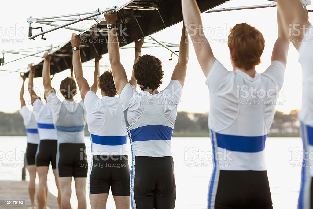 Rear view of men holding row boat overhead stock photo