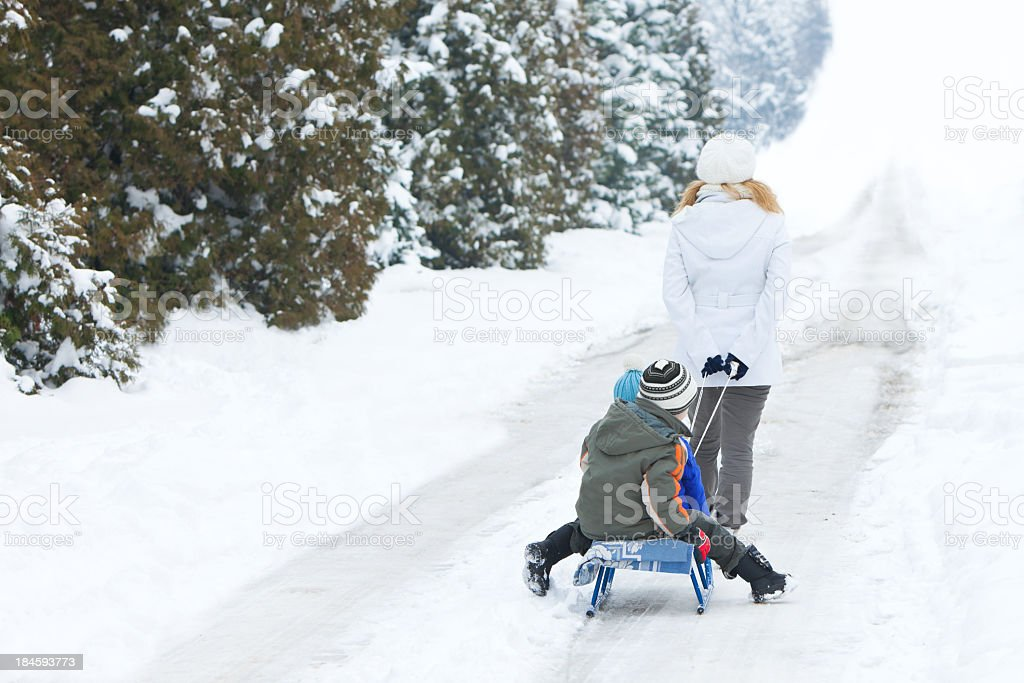 Rear View OF Mother Pulling Her Sons On Sled stock photo