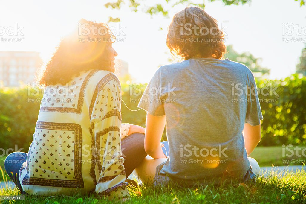 Rear view of mother sharing music sitting with teenager son stock photo