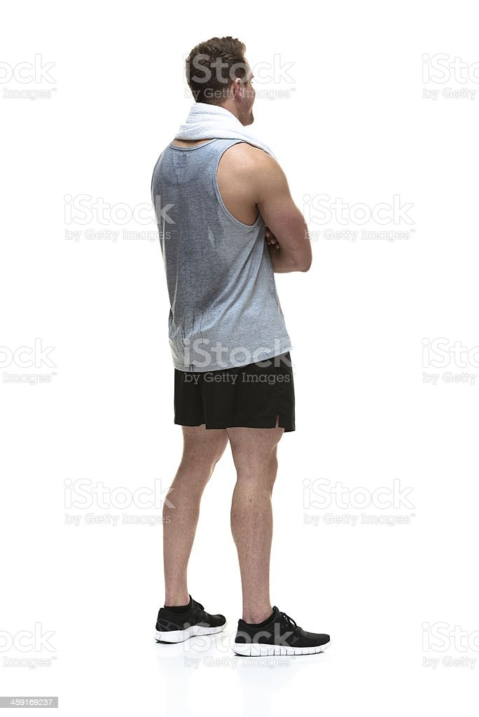 Rear view of muscular man with arms crossed stock photo