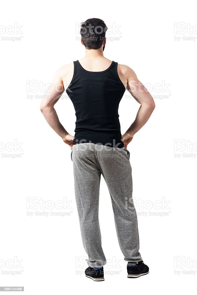 Rear view of muscular sporty man with arms on hips stock photo