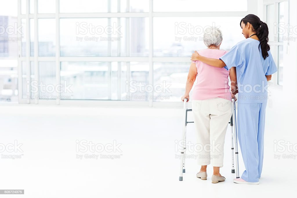 Rear View Of Nurse Assisting Senior Patient With Walker stock photo