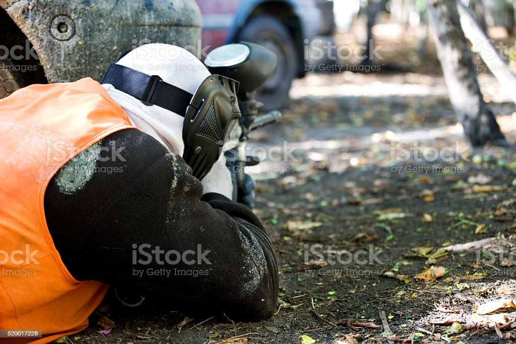 rear view of paintball player aiming at hidden target stock photo