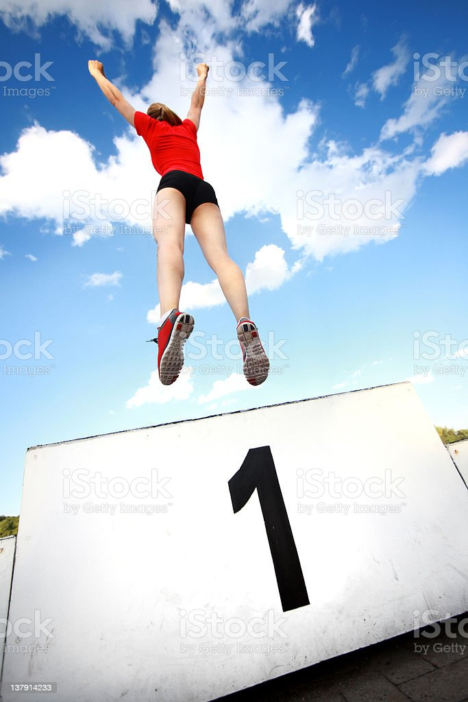 Rear view of person jumping over white sign with number one. stock photo