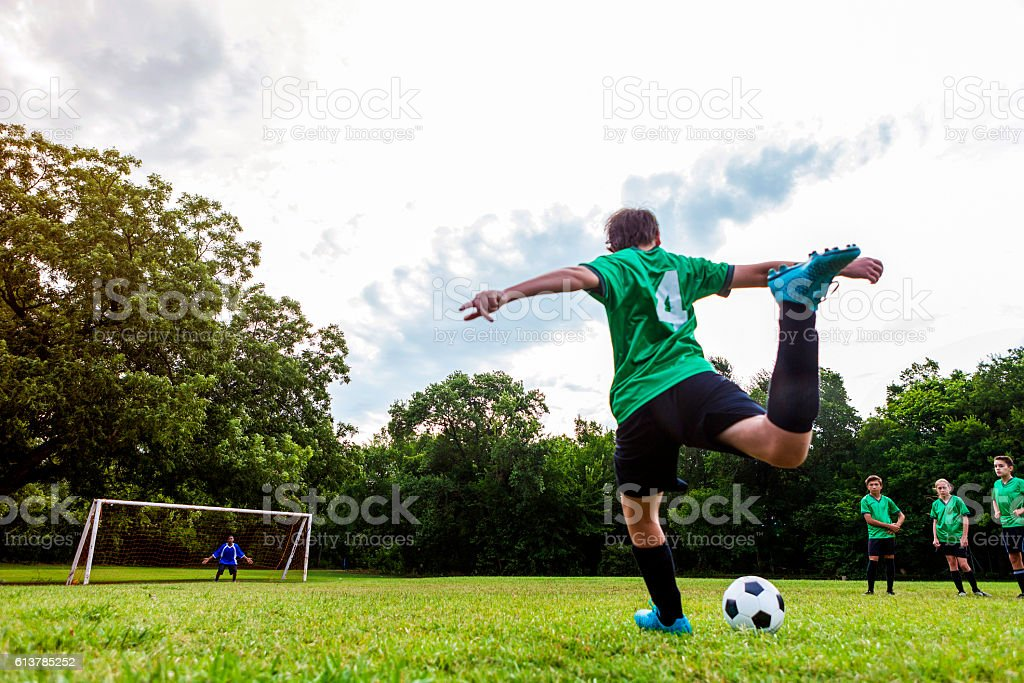 Rear view of player taking penalty shot stock photo