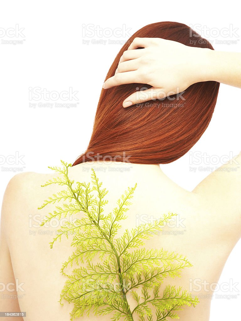 Rear view of redhead woman with a green fern leaf royalty-free stock photo