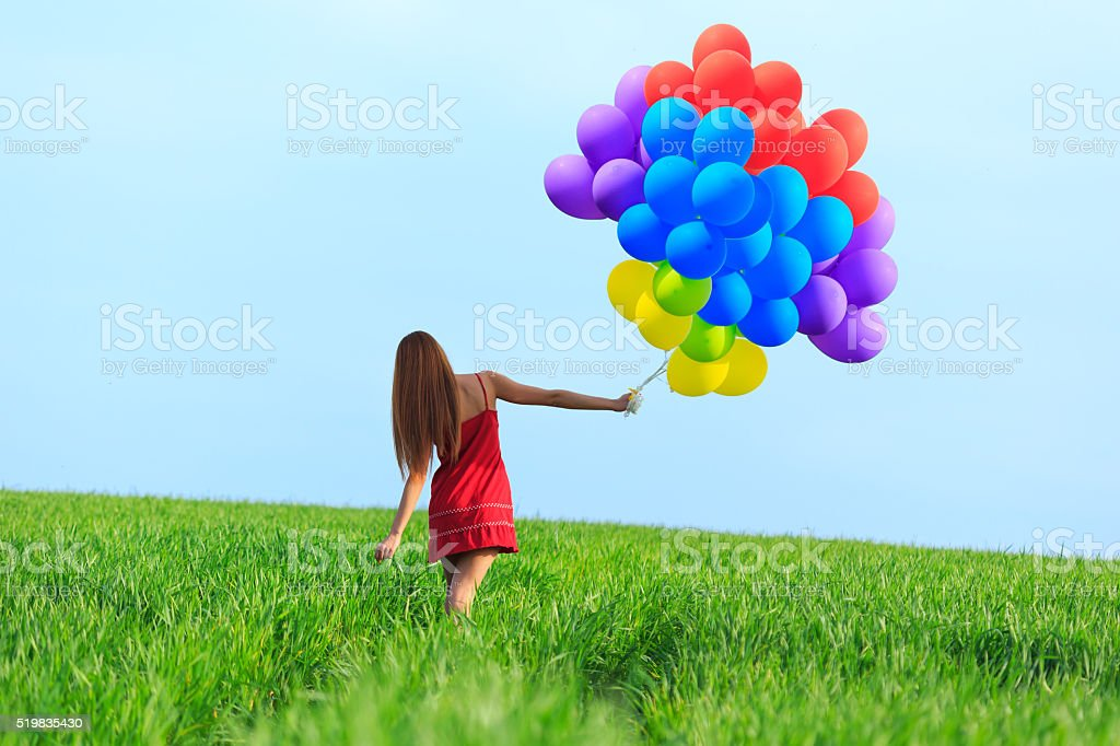 Rear view of redheaded young woman dancing with colored balloons stock photo