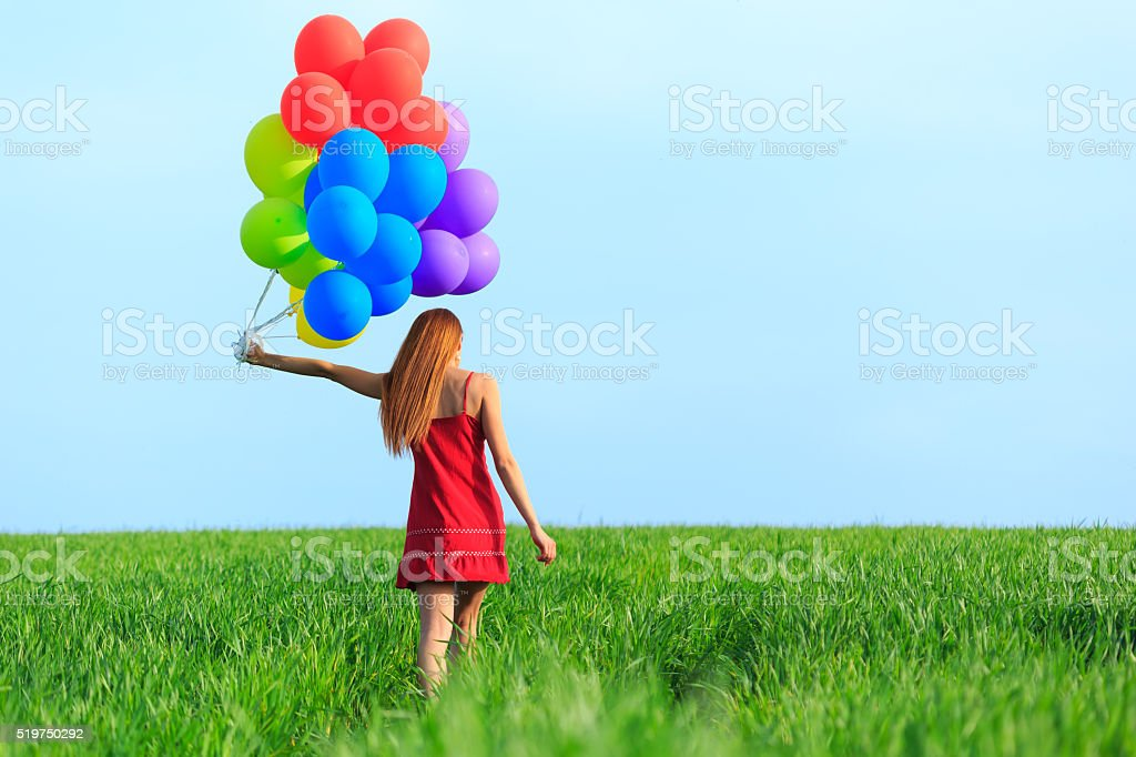 Rear view of redheaded young woman with colored balloons stock photo
