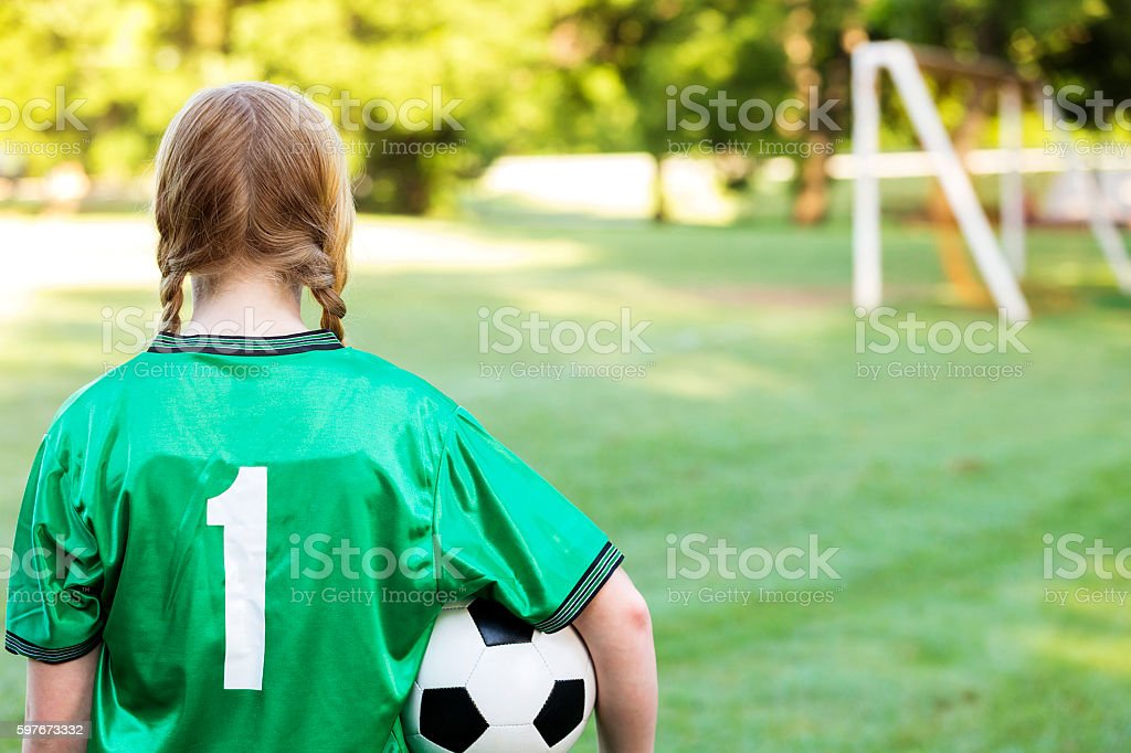 Rear view of reflective soccer player thinking about the game stock photo