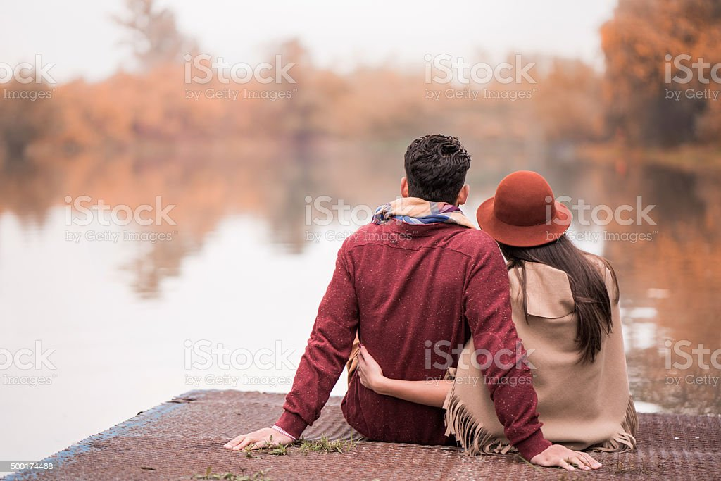 Rear view of romantic couple on a pier in autumn. stock photo