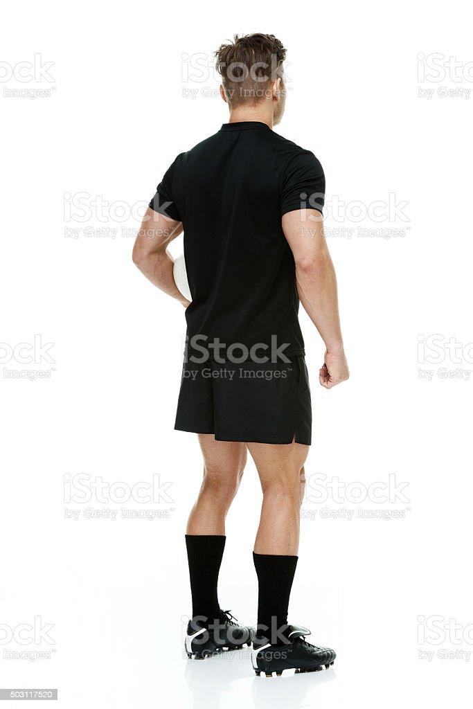 Rear view of rugby player holding ball stock photo