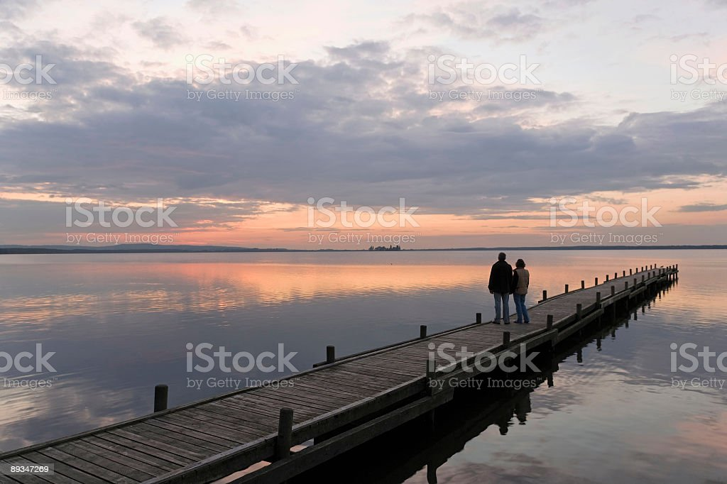 Rear view of Senior couple on lakeside jetty at sunset stock photo